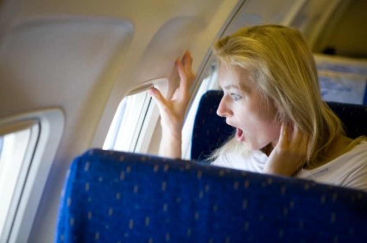 Woman looking out of aircraft window terrified