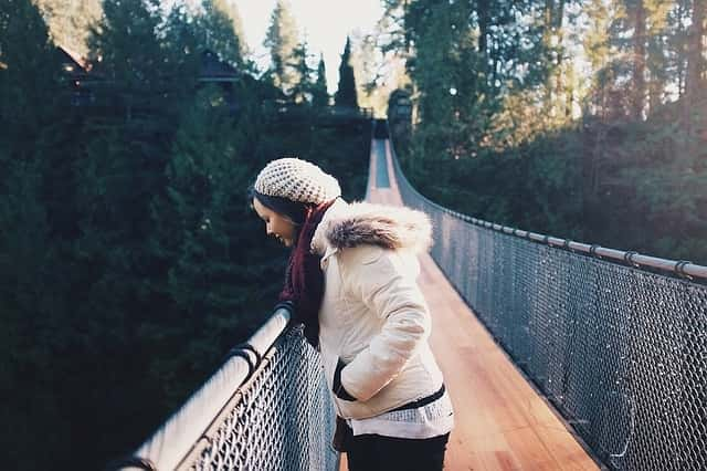 woman standing on bridge looking down suffering from Acrophobia