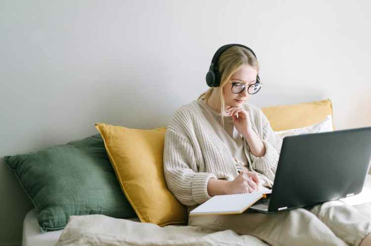 Woman sitting in front of laptop writing affirmations.