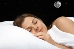 Sleeping woman in bed listening to subliminal affirmations.