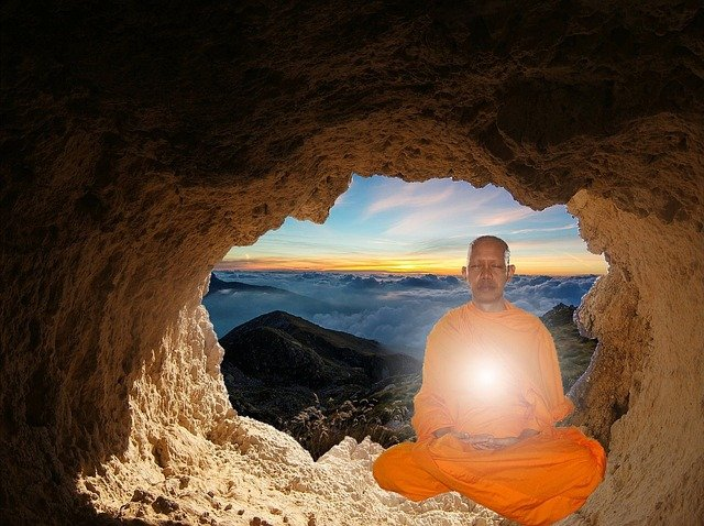 Monk meditating in cave with solar plexus on body glowing.