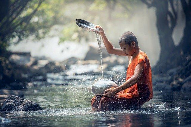 Monk sitting in river in orange robe.